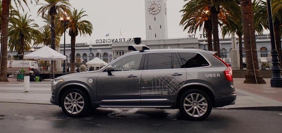 A Volvo SUV with Uber markings and self-driving sensor hardware visible is shown in San Francisco.