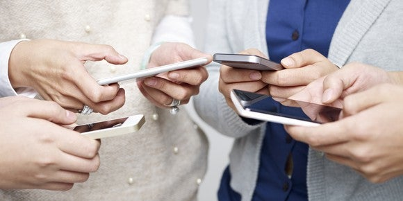 A group of adults huddled over their smartphones.