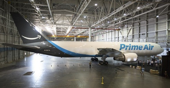 "A Boeing 767-300 freight airliner with Amazon's ""Prime Air"" markings, in a hangar."