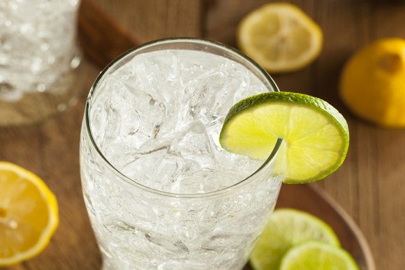 A sparkling soda beverage in a glass, garnished with a lime.