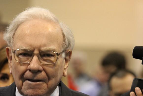 Warren Buffett walking through a crowd past cameras.