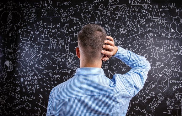 confused man staring at complicated equations on a blackboard