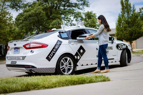 A woman takes pizzas from a self-driving Ford Fusion Hybrid pizza-delivery test vehicle at a curb in front of a house.