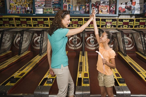 A mom and daughter high-five in front of a skee-ball game.