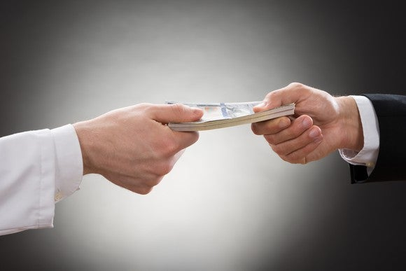 Hand in white sleeve holding money on one end with hand in dress shirt and coat holding other end