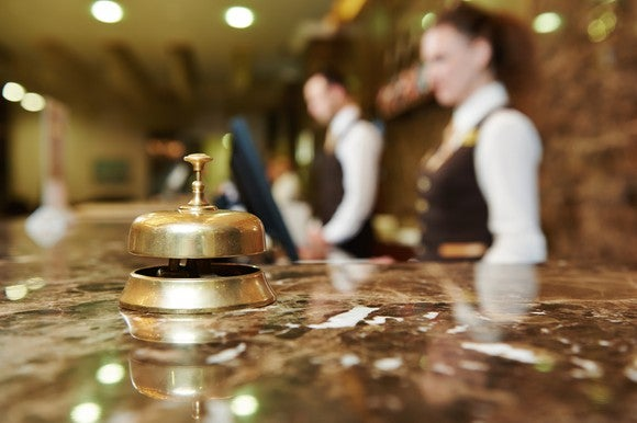 A brass bell sits on the front desk of a hotel, with two employees in the background.