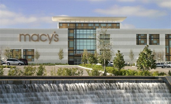 The exterior of a Macy's store, with a manufactured waterfall in the foreground.