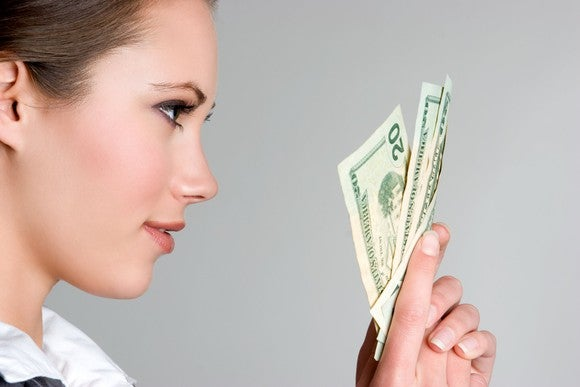 A woman holding $20 bills.