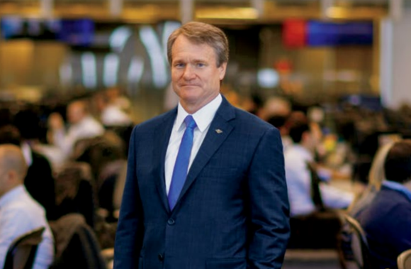 Bank of America's CEO Brian Moynihan, standing in front of two rows of desks.