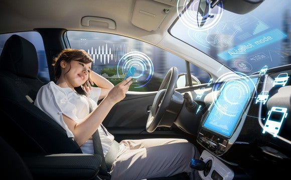 A woman uses her smartphone in an autonomous car.