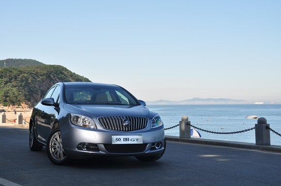 A Chinese-market Buick Excelle GT sedan with a Chinese-language license plate is shown parked by the ocean.