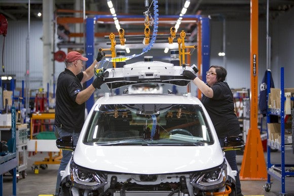 Workers fit self-driving sensors to the roof of a Chevrolet Bolt EV on an assembly line at General Motors' Orion Assembly Plant in Orion Township, Michigan.
