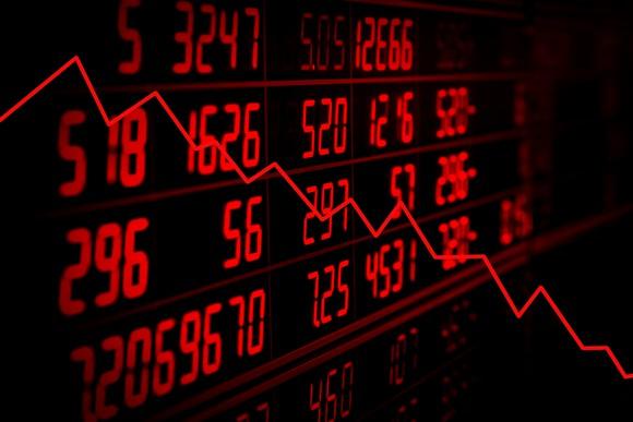Downward trend arrow with stock ticker board in background.