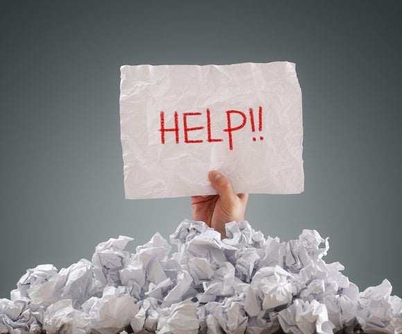 Person buried under paper holding 'help' sign