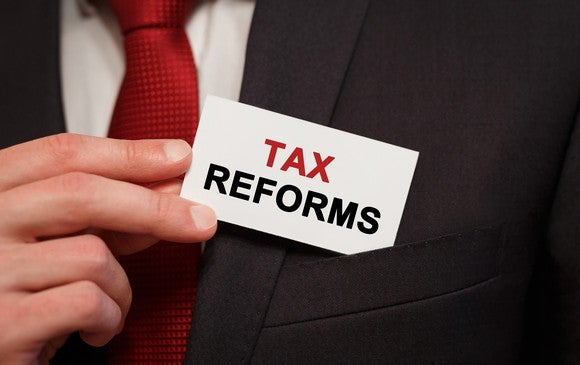 "A businessman in a suit pulling a business card from his pocket that reads ""tax reforms."""