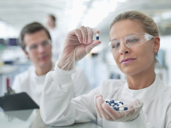A biotech lab researcher holding up and examining a drug capsule.