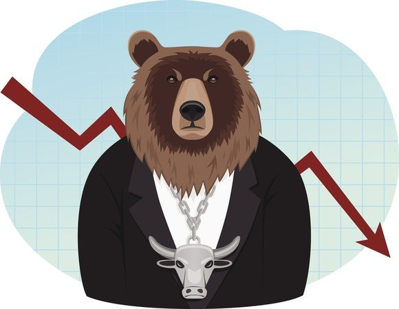 A cartoon bear (representing a down market) wearing a necklace of a bull (representing an up market) sitting in front of a red arrow heading down.
