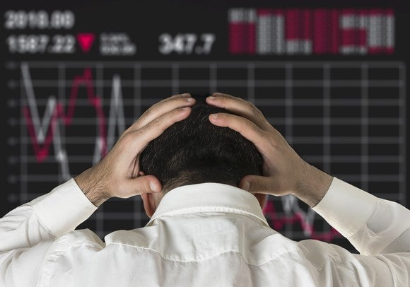A man holds his head in his hands as he watches a screen showing a declining stock price.