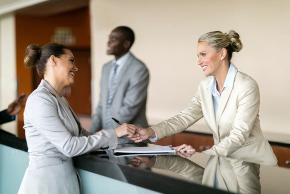 A woman checking in at a hotel reception desk