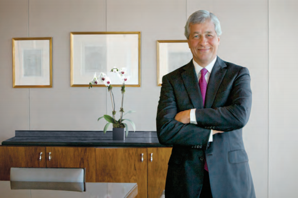Jamie Dimon, chairman and CEO of JPMorgan Chase, standing in an office with his arms crossed.