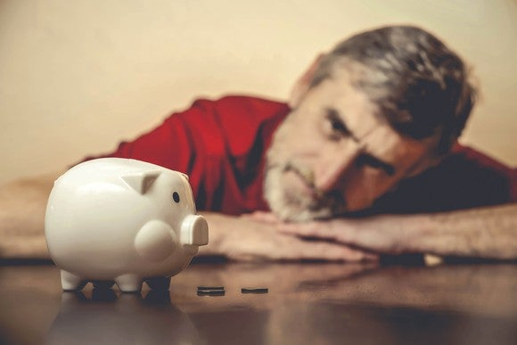 A senior staring worryingly at his piggy bank.