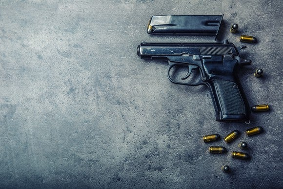 Gun with clip and bullets sitting on a granite counter.