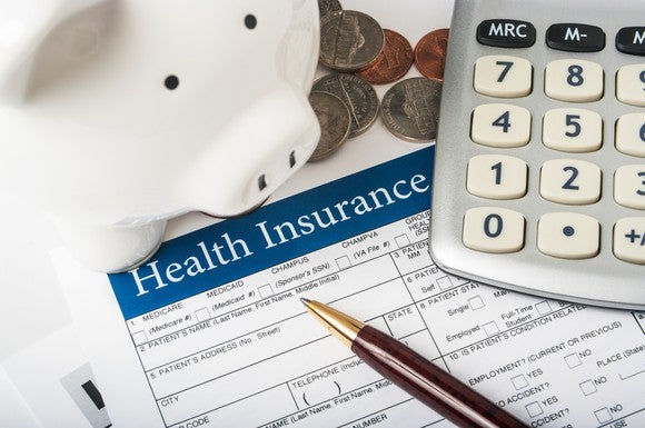 Health insurance form with pen, calculator, piggy bank, and coins