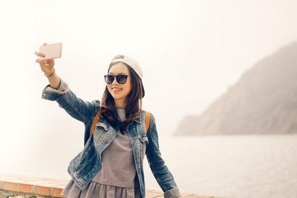 An Asian traveler takes a selfie with her smartphone.