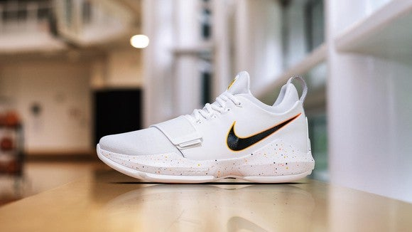 Nike's Paul George basketball shoes in white with a black and orange swoosh.