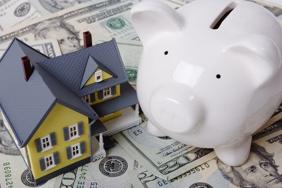 A model-sized house and piggy bank sitting on a pile of cash.