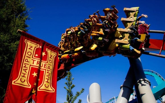 "Dragon Challenge's ""fire"" coaster riding by a True Champion banner."