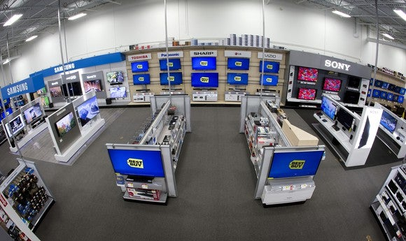 A view of a Best Buy home theater department, with TVs displayed on the wall and on two end caps.
