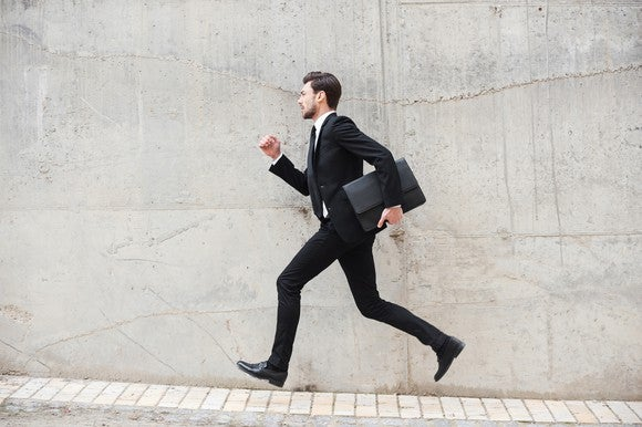 A businessman, who appears to be in a hurry, carrying a briefcase.
