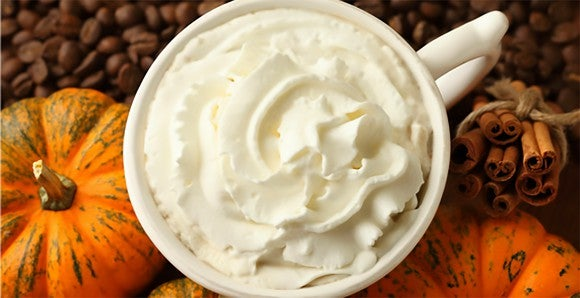 An overhead shot of a Starbucks Pumpkin Spice Latte, showing the whipped cream topping. Gourds, coffee beans, and cinnamon sticks are also on the table.