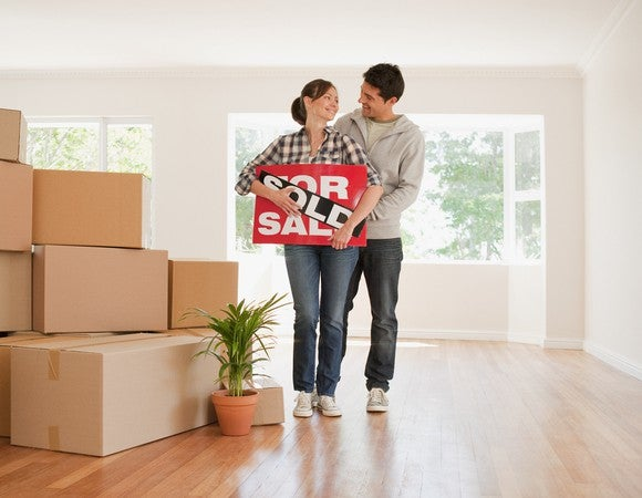Young couple holding sold sign in a living room filled with boxes.