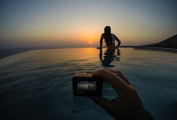 Person holding camera taking a picture of a woman at sunset