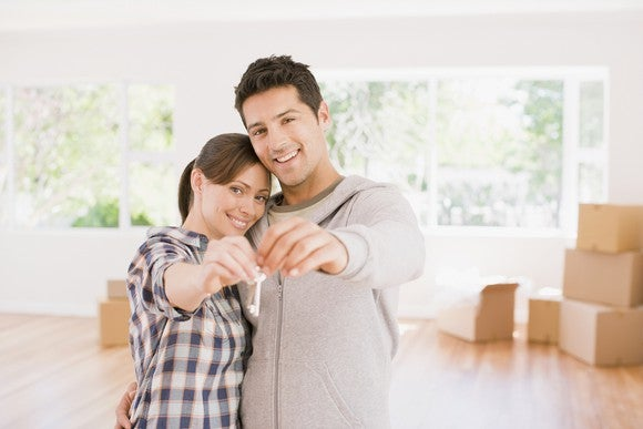 A young couple holding a key in a room with packed boxes.