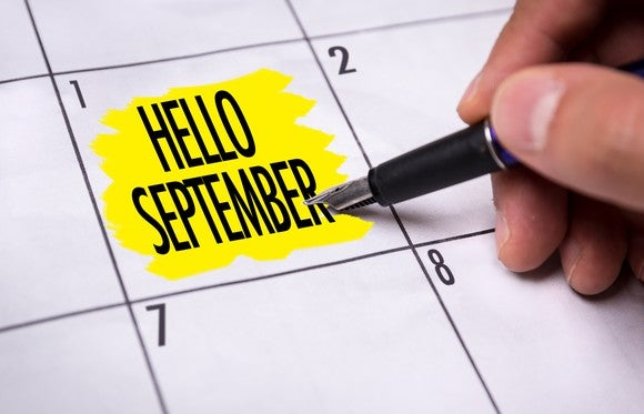 "Hand holding pen next to words ""Hello September"" highlighted in yellow on calendar"