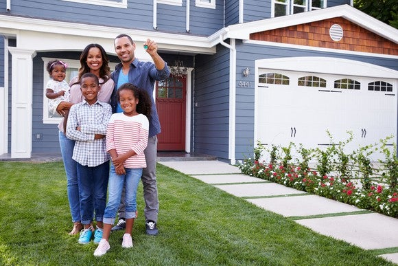 Family standing in front of new home.