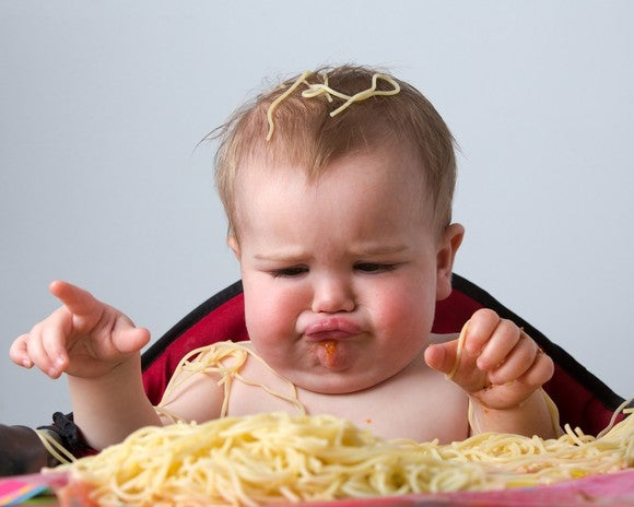 Frowning baby sitting in high chair eating spaghetti noodles with hands and making a mess.