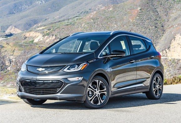 A black 2017 Chevrolet Bolt EV parked outside on a sunny day with mountains in the background.