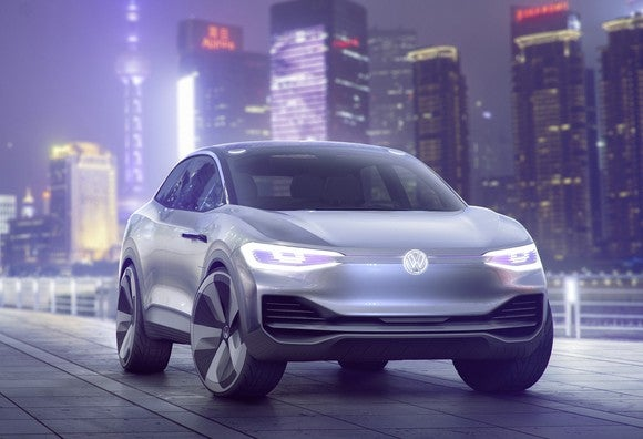 The first VW I.D. Crozz show car, a futuristic-looking silver SUV, is shown at night with Shanghai's skyline in the background.