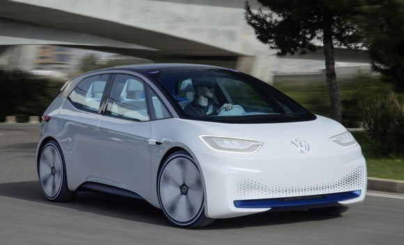 The Volkswagen I.D. Concept, a futuristic-looking white hatchback with a black roof, on a road.