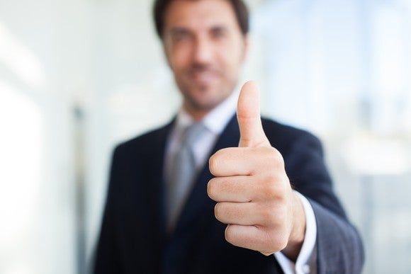 A man in a suit gives a thumbs up