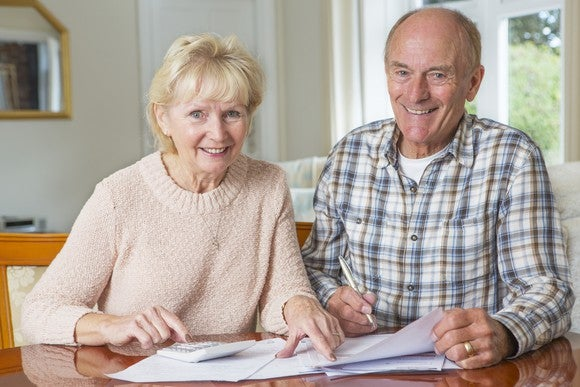 An older couple sits smiling at a table as they review a stack of papers. The woman has a calculator and the man holds a pen.
