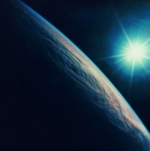 Image of Earth from orbit with sun in background.