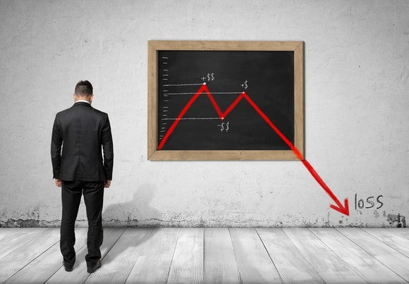 A businessman looking into the field of view with his head down, a red chart showing losses is drawn on a chalkboard.