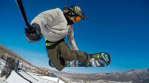 A snowboarder holding a GoPro camera on a stock while wearing one on his head.
