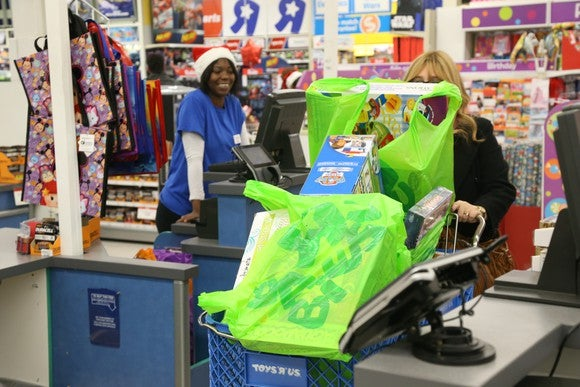 A shopper leaving a Toys R Us with a shopping cart full of bags.
