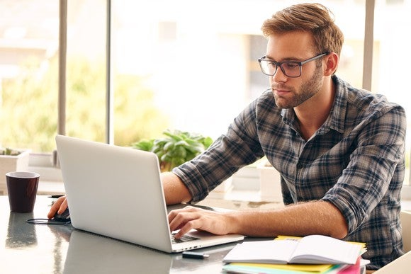 Male student wearing glasses, using a laptop